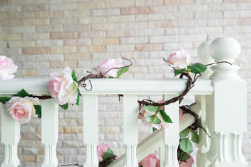 close-up of railing staircase covered with artificial rose and ivy.