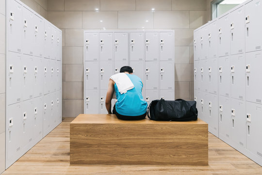 man with towel sitting on wooden bench in gym - prepare for workout.