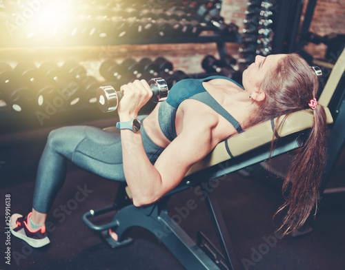Young Woman In Sportswear Doing Exercise With Dumbbells For The