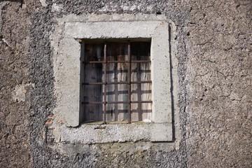 Old stone window with iron cross