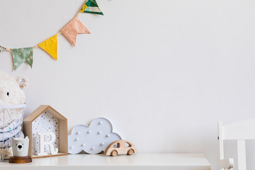 Stylish and cozy childroom with design toys, cloud and hanging cotton flags. Modern scanidnavian interior with white background wall. Copy space for inscription or product. Real phote. Template.