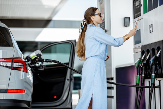 Woman paying with phone for gasoline, photographing bar code on the gas station pump
