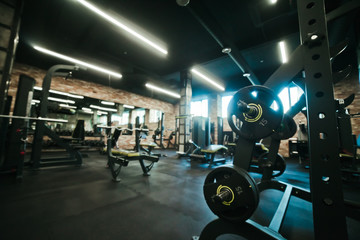 Gym equipment. Dark Gym with barbells on rack. Fitness workout center. Sport concept.
