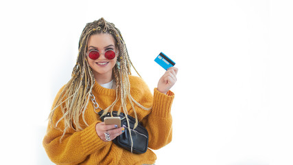 Keuken foto achterwand Extravagant plus size young woman with glasses holding a smartphone and a credit card in her hands.