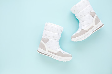 Wall Mural - White women winter boots isolated on blue background. Flat lay, top view trendy fashion feminine background. Beauty blog concept. Fashion blog look.