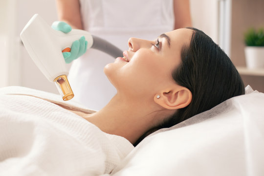 Dark haired woman smiling during the laser treatment