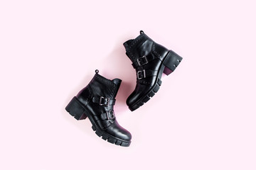 Wall Mural - Black female boots on pink background. Flat lay, top view minimal background. Fashion blog or magazine concept.