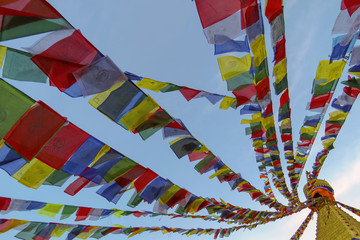 Colorful buddhist prayer flags swaying in the wind, attached to the top of Boudhanath stupa, Kathmandu, Nepal
