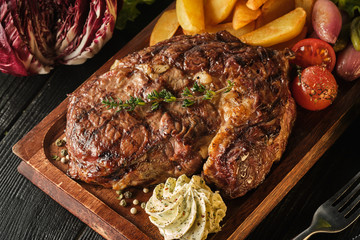 Ribeye steak with potatoes, onions and baked cherry tomatoes. Juicy steak with flavored butter