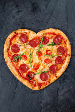 Heart shaped pizza with meat and vegetables. Food concept of romantic love for Valentines Day.