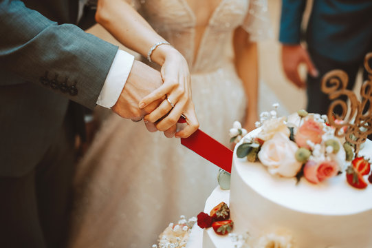 Photo of happy couple bride and groom cutting a wedding cake