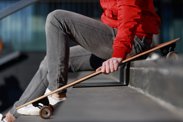 Stylish man longboarder in casual clothes resting on the steps, sitting with longboard/skateboard outdoors, side view, cropped image. Urban, subculture, skateboarding concept