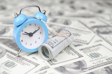 Time as an important business resource. Blue alarm clock and dollar bills