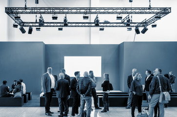Fototapete - business people walking between trade show booths at a public event exhibition hall and copy space for individual text