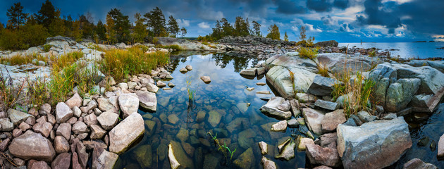 Russia. Karelia. The rocky shore of the island. Rocky river. Large stones flooded with water. Karelian landscape. Wildlife panorama. Stony shore on Lake Ladoga. Ladoga lake. Fototapete
