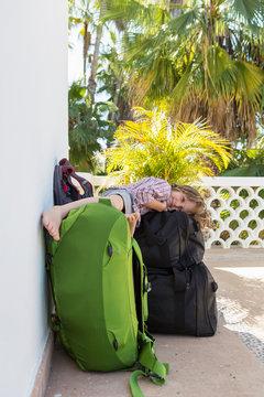 portrait of 5 year old boy lying on travel luggage, Todos Santos, Mexico