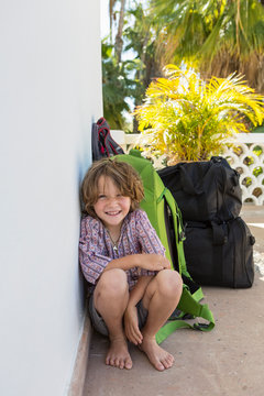 portrait of 5 year old boy leaning on travel luggage, Todos Santos, Mexico