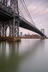 Williamsburg bridge from east river at sunrise with long exposure