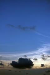 In de dag Landschap Cloudscape background of a single dark cloud against an otherwise clear blue sunset sky.