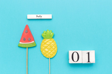 Wooden cubes calendar July 1. Summer fruits pineapple, watermelon on blue background. Concept hello July Copy space Creative Top view Flat lay