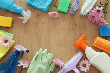 Spring cleaning concept with supplies over wooden background. Top view, flat lay