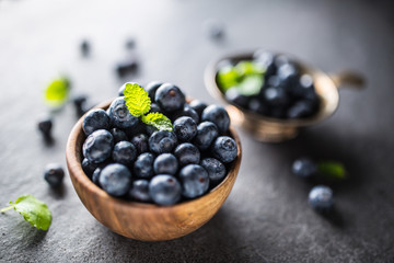 Wooden bowl full of fresh blueberries with herbs