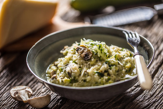 Italian risotto zucchini mushrooms and parmesan in dark plate