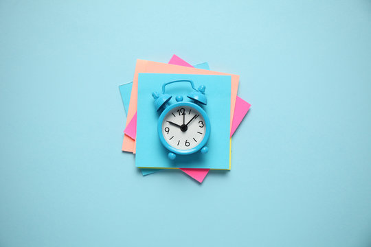 Blue alarm clock and paper reminder. Time management, priorities, efficiency, control and goals.