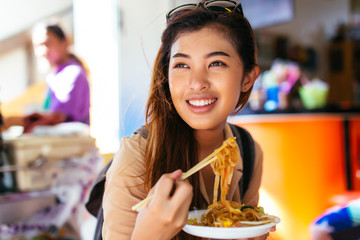 Young Asian tourist woman eating pad thai noodle, traditional street food in Thailand and looking far away