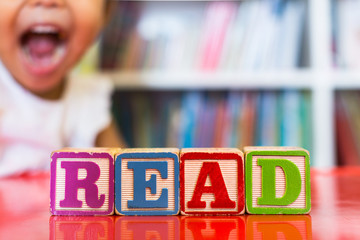 Alphabet blocks spelling the word read in front of a bookshelf and an excited child in the...