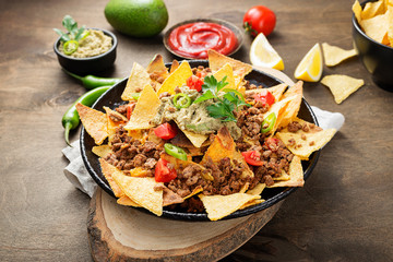 Corn chips nachos with fried minced meat and guacamole on wooden background.