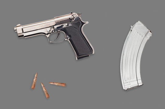 New glossy metal pistol near bullets for assault rifle on gray table. Top view. Protection concept