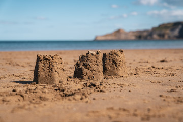 Sandcastles on the beach of Runswick Sands, North Yorkshire England, UK - with Kettleness in the background