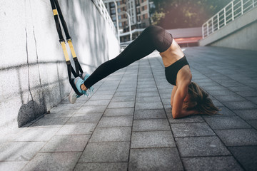 Young beautiful woman working out with suspension straps