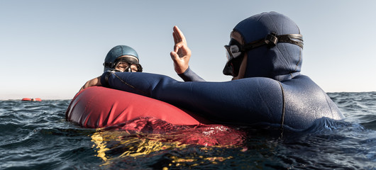 Wall Mural - Freediver performs consciousness check on the buoy and shows Ok sign to the buddy after deep dive