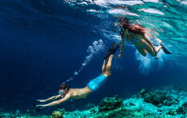 Fototapeta Young couple snorkeling and do skin diving on the coral reef edge in tropical waters of the Maldives obraz