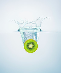 slice of kiwi falls into the water scattering a lot of splashes and drops