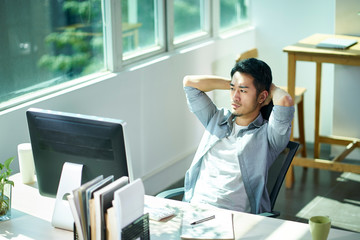young asian businessman thinking in office