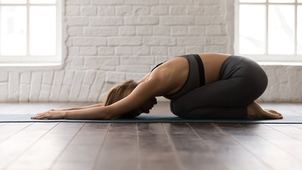 In de dag Ontspanning Young woman practicing yoga, lying in Child pose, Balasana exercise