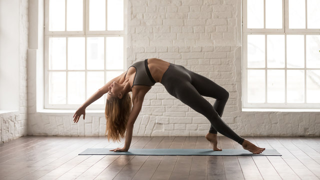 Young woman practicing yoga, standing in Wild Thing pose, Camatkarasana