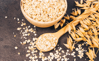 Oatmeal - a component of a healthy diet, on a dark background.