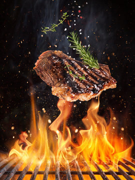 Tasty beef steaks flying above cast iron grate with fire flames.