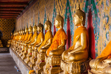 A gallery of the statues of dressed seated Buddhas in Wat Arun, Bangkok