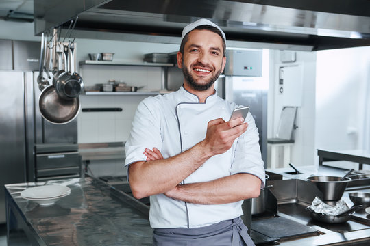 The master of kitchen. Happy chef cook standing in commerical kitchen