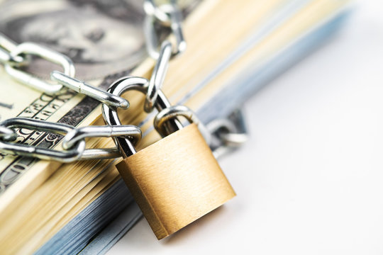 Business safety or financial protection or restriction access. Heap of money in chain with padlock isolated on white