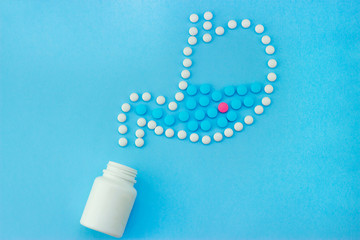 A jar of scattered pills in the form of the stomach on a blue background
