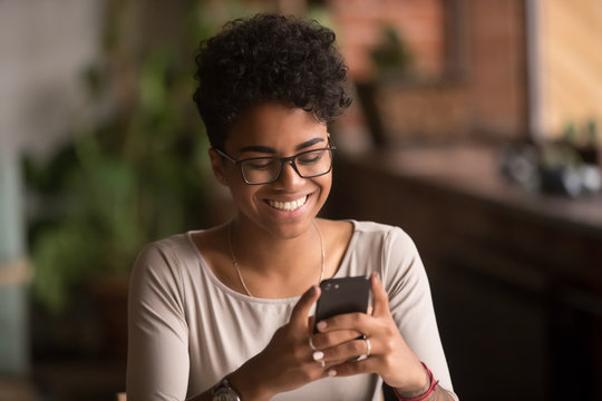Happy millennial african american woman holding smartphone using ecommerce apps