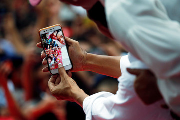 Indonesia's president and presidential candidate for the next election Joko Widodo and his wife Iriana Widodo take selfie pictures with their supporters at a carnaval during a campaign rally in Tangerang