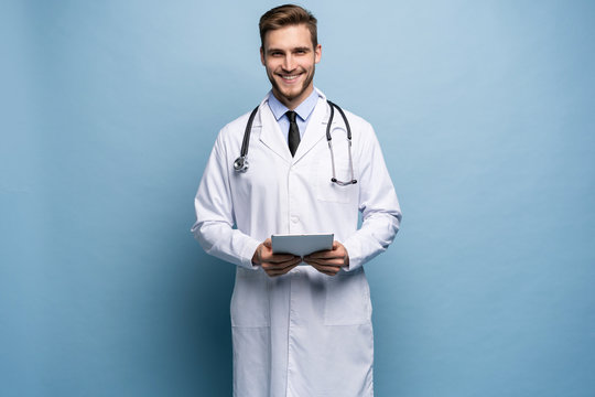 Portrait of confident young medical doctor on blue background.