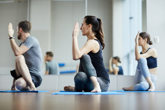 Group of young yoga students concentrated on exercise sitting on mats and performing seated spinal twist at class